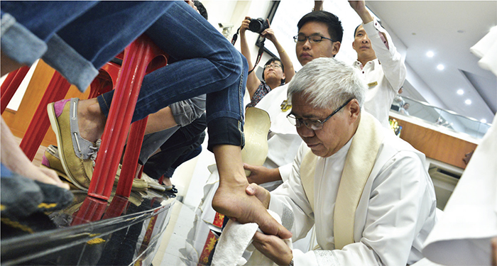 Archbishop William Goh washes the feet of a parishioner. Photo: VITA Photo