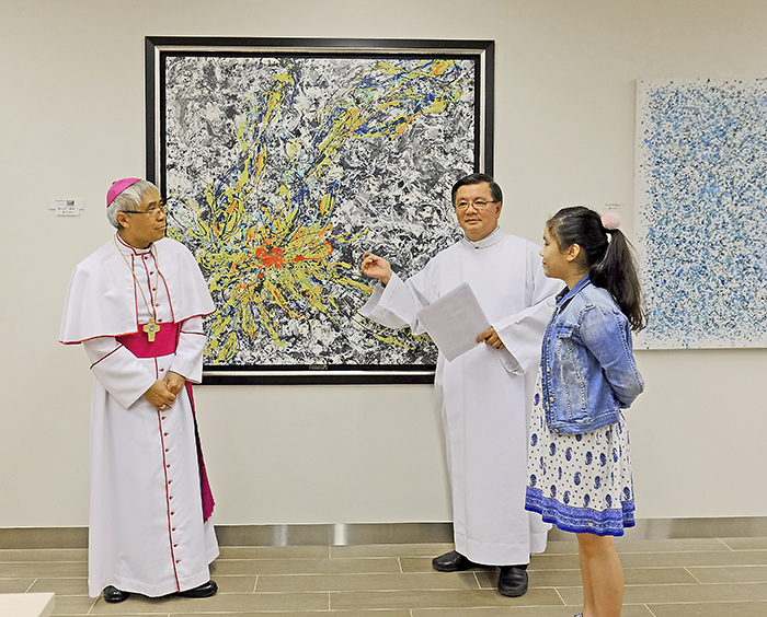 Archbishop William Goh and Msgr Philip Heng presents 12-year-old Ashley Tan's (right) painting at a fundraising auction. Photo: Vita Images.